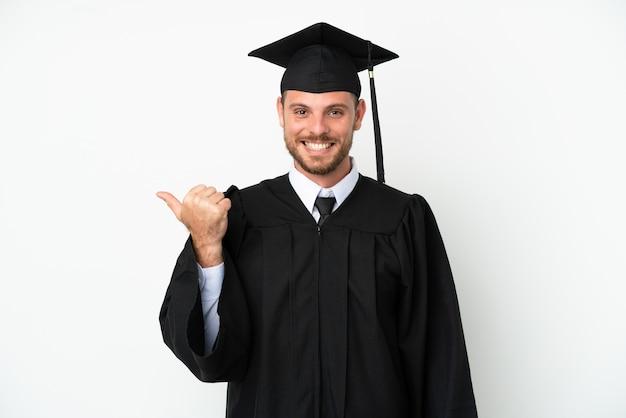 제품을 제시하기 위해 측면을 가리키는 흰색 배경에 고립 된 젊은 대학 브라질 졸업생