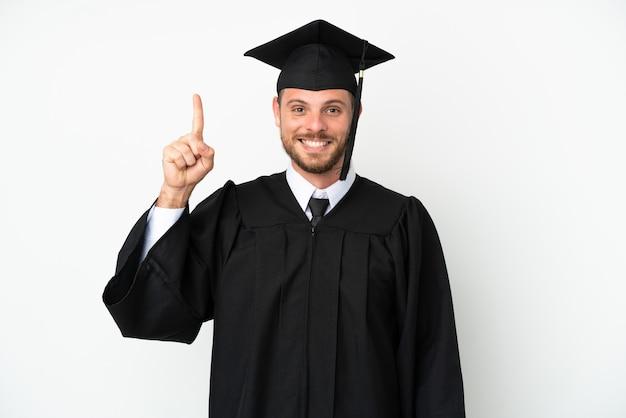 Молодой бразильский выпускник университета изолирован на белом фоне, указывая на отличную идею