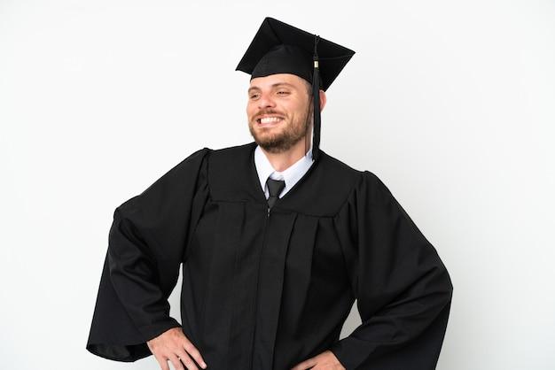 Молодой бразильский выпускник университета изолирован на белом фоне позирует с руками на бедрах и улыбается