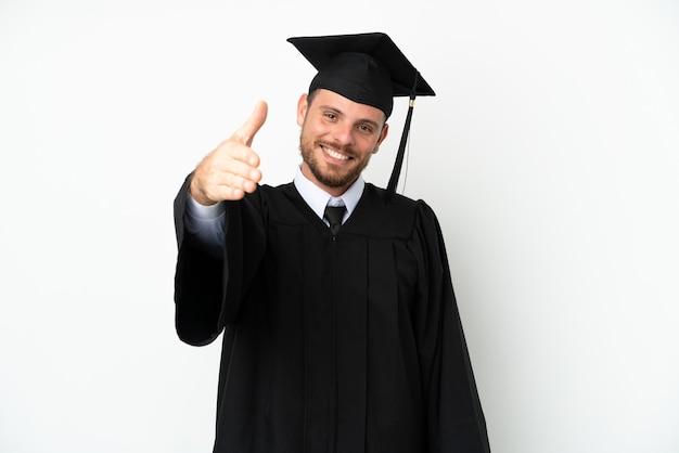 젊은 대학 브라질 졸업생은 좋은 거래를 마감하기 위해 악수하는 흰색 배경에 고립