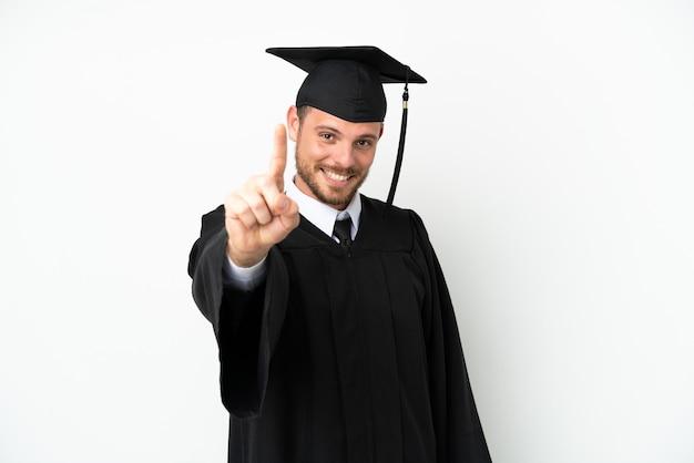 Молодой бразильский выпускник университета изолирован на белом фоне, показывая и поднимая палец