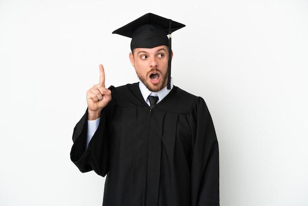Молодой бразильский выпускник университета изолирован на белом фоне, думая об идее, указывая пальцем вверх
