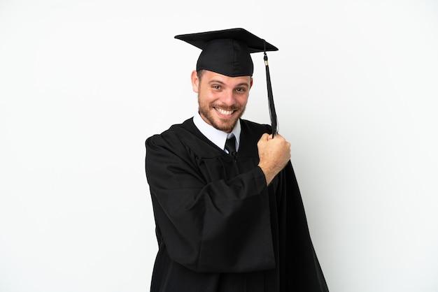 Young university brazilian graduate isolated on white background celebrating a victory
