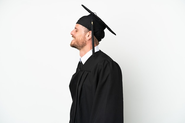 Young university brazilian graduate isolated on white background laughing in lateral position