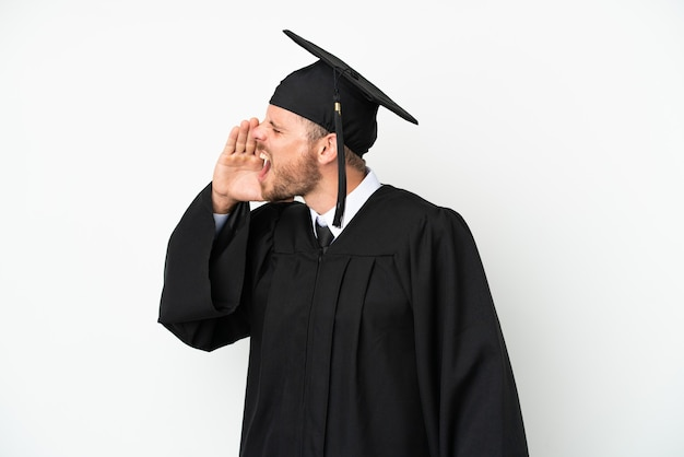Young university brazilian graduate isolated on white background shouting with mouth wide open to the side