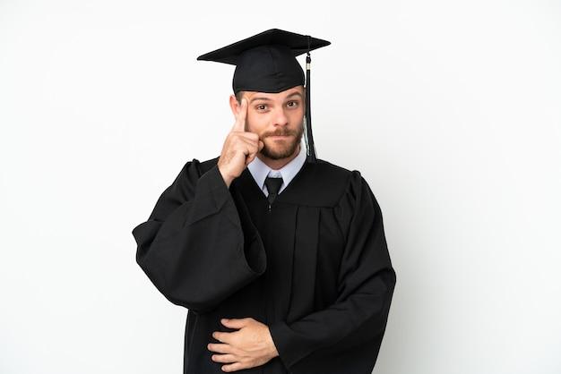 Young university brazilian graduate isolated on white background thinking an idea