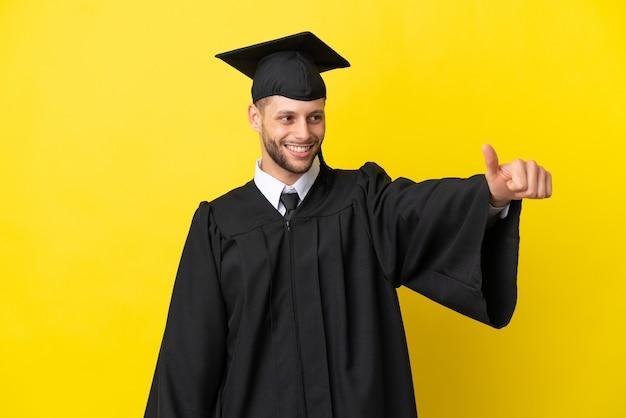 Молодой выпускник университета кавказский человек изолирован на желтом фоне, показывая большой палец вверх жест