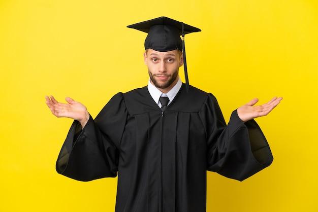 Молодой выпускник университета кавказский мужчина изолирован на желтом фоне, сомневаясь, поднимая руки