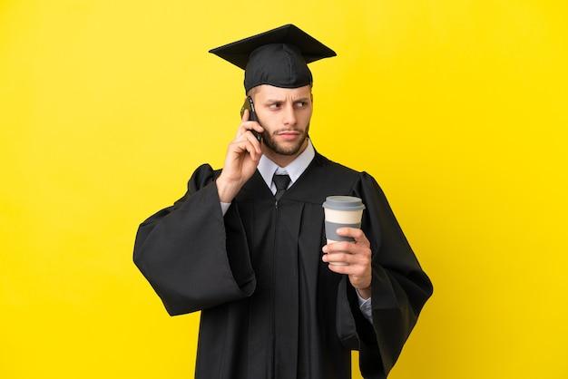 Молодой выпускник университета кавказский мужчина изолирован на желтом фоне, держа кофе на вынос и мобильный