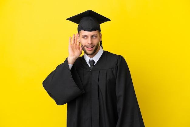 귀에 손을 대고 뭔가를 듣고 노란색 배경에 고립 된 젊은 대학 졸업 백인 남자