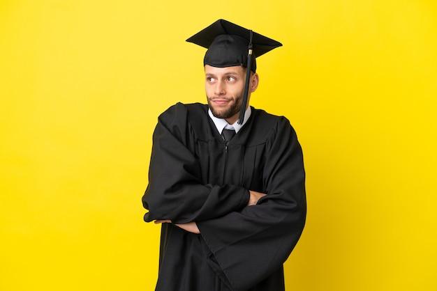 노란색 배경에 격리된 젊은 대학 대학원 백인 남자가 어깨를 들어올리는 동안 의심스러운 제스처를 취합니다.