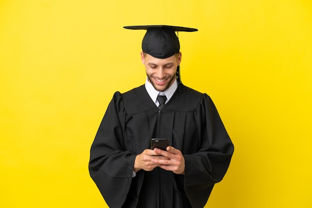 携帯電話でメッセージを送信する黄色の背景に分離された若い大学卒業生の白人男性
