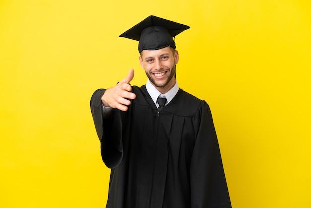 Молодой выпускник университета кавказский мужчина изолирован на желтом фоне, пожимая руку для заключения хорошей сделки