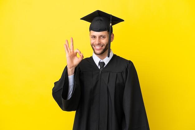 Молодой выпускник университета кавказский мужчина изолирован на желтом фоне, показывая пальцами знак ок