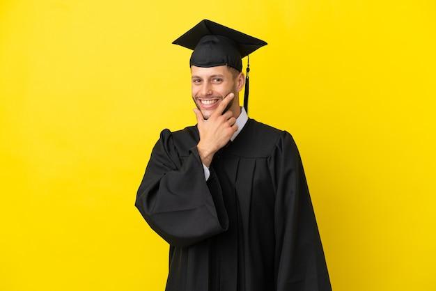 Молодой выпускник университета кавказский человек изолирован на желтом фоне улыбается