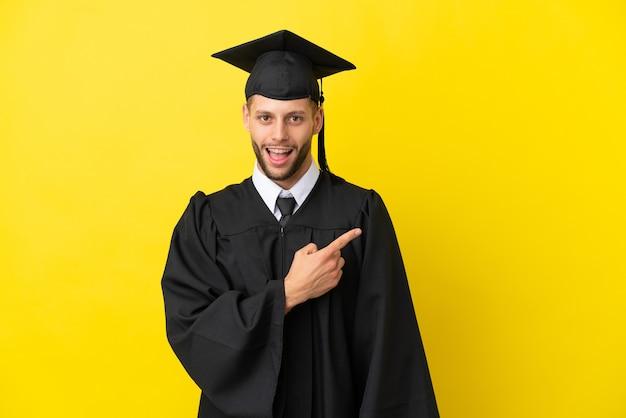 Молодой выпускник университета кавказский человек изолирован на желтом фоне удивлен и указывает сторону