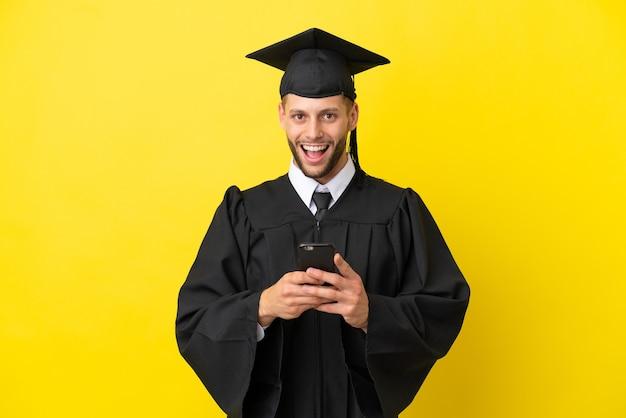 Молодой выпускник университета кавказский мужчина изолирован на желтом фоне удивлен и отправляет сообщение