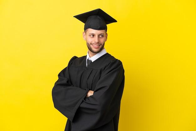 Молодой выпускник университета кавказский мужчина изолирован на желтом фоне со скрещенными руками и счастливым
