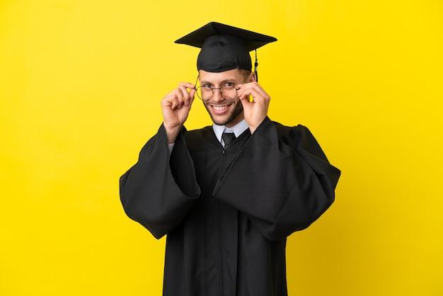 Молодой выпускник университета кавказский мужчина изолирован на желтом фоне в очках и удивлен