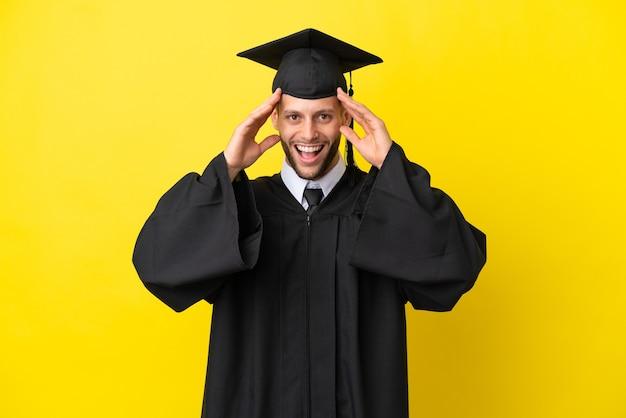 Молодой выпускник университета кавказский мужчина изолирован на желтом фоне с удивленным выражением лица