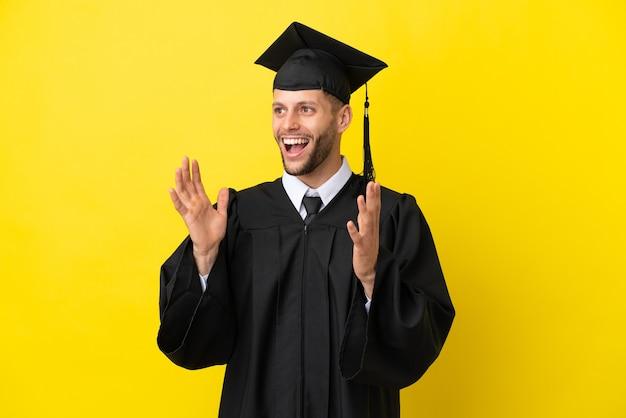놀람 표정으로 노란색 배경에 고립 된 젊은 대학 대학원 백인 남자