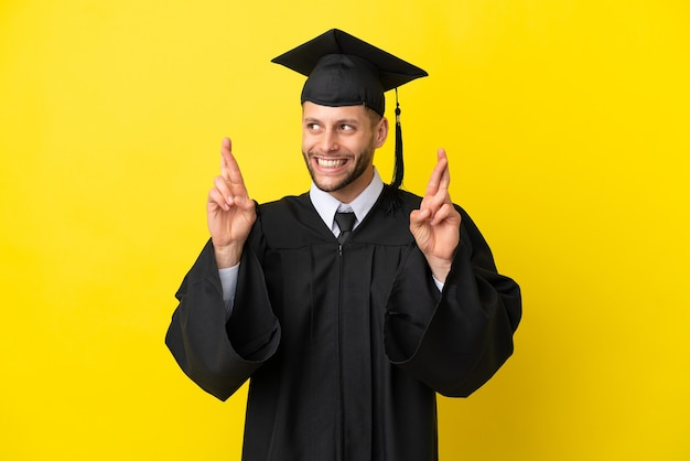 Young university graduate caucasian man isolated on yellow background with fingers crossing