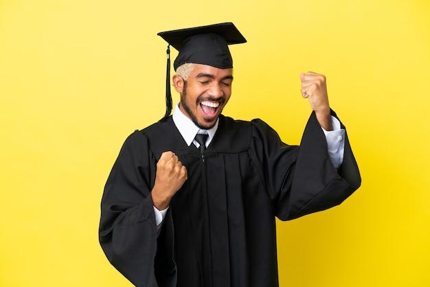 Колумбийский молодой выпускник университета изолирован на желтом фоне празднует победу