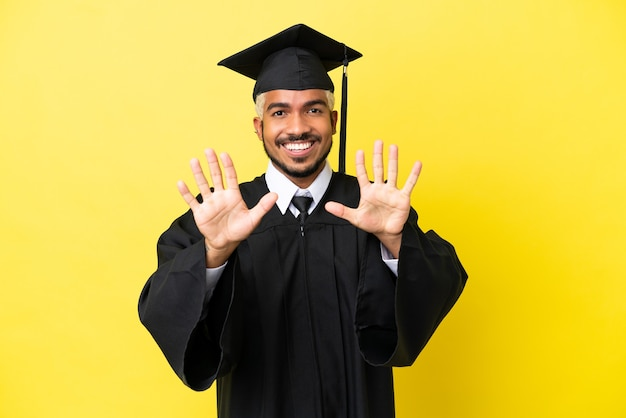 Молодой выпускник университета колумбиец изолирован на желтом фоне, считая десять пальцами