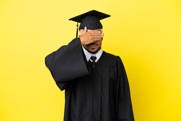 Колумбиец молодой выпускник университета изолирован на желтом фоне, закрывая глаза руками. не хочу что-то видеть
