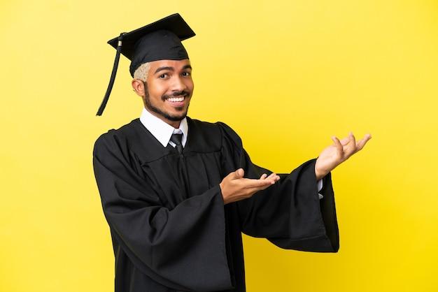 Молодой выпускник университета колумбиец изолирован на желтом фоне, протягивая руки в сторону, чтобы пригласить приехать