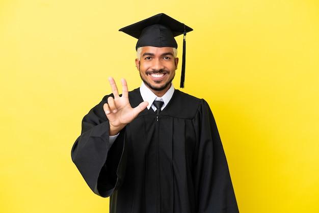 Молодой выпускник университета колумбиец изолирован на желтом фоне счастлив и считает три пальцами
