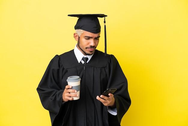 Молодой выпускник университета колумбиец изолирован на желтом фоне, держа кофе на вынос и мобильный