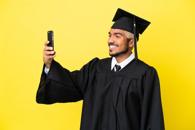 셀카를 만드는 노란색 배경에 고립 된 젊은 대학 졸업생 콜롬비아 남자