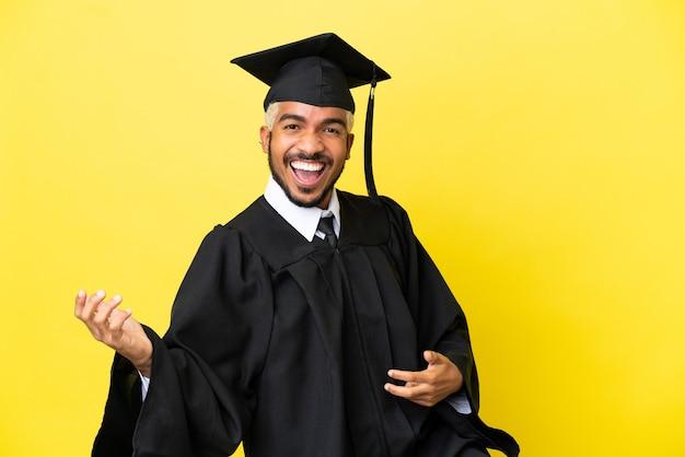 Молодой колумбийский выпускник университета изолирован на желтом фоне, делая жест гитары