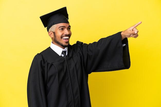 Колумбийский молодой выпускник университета изолирован на желтом фоне, указывая в сторону