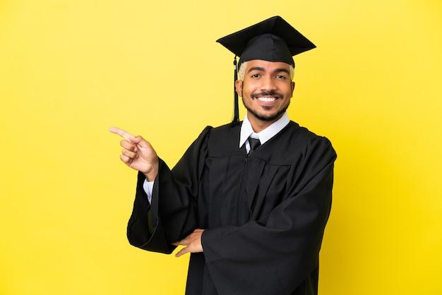 Молодой выпускник университета колумбиец изолирован на желтом фоне, указывая пальцем в сторону