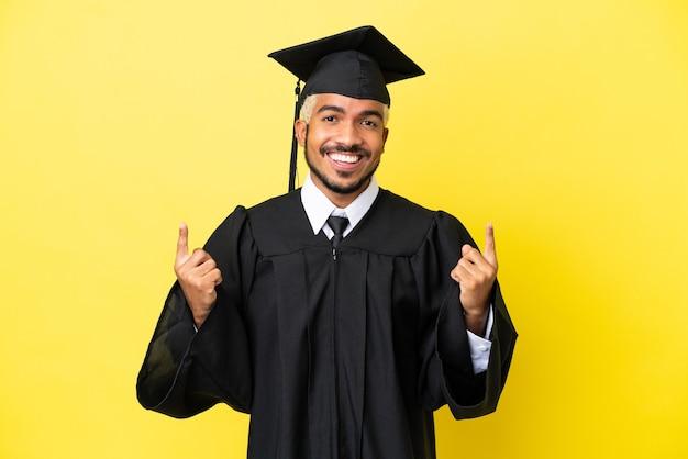 Молодой колумбийский выпускник университета изолирован на желтом фоне, указывая на отличную идею