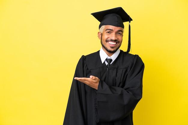 Молодой колумбийский выпускник университета изолирован на желтом фоне, представляя идею, глядя в сторону