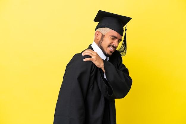 Молодой колумбийский выпускник университета изолирован на желтом фоне и страдает от боли в плече за то, что приложил усилие
