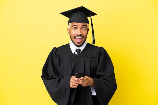 Молодой выпускник университета колумбиец изолирован на желтом фоне удивлен и отправляет сообщение