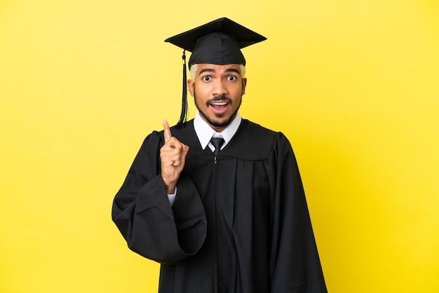 Молодой колумбийский выпускник университета изолирован на желтом фоне, думая об идее, указывая пальцем вверх