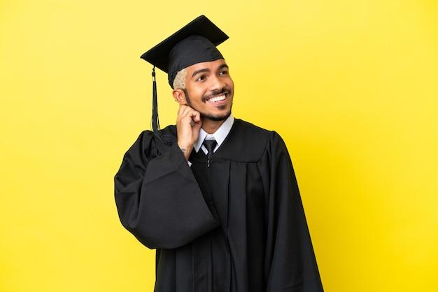 Колумбийский молодой выпускник университета изолирован на желтом фоне, думая об идее