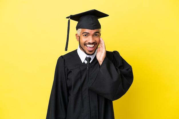놀람과 놀란 표정으로 노란색 배경에 고립 된 젊은 대학 졸업생 콜롬비아 남자