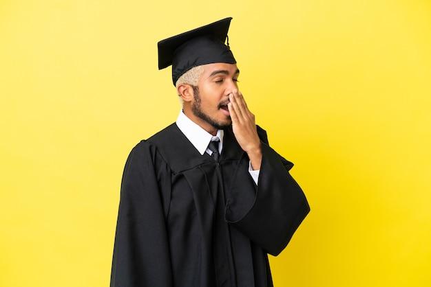 あくびをし、手で大きく開いた口を覆う黄色の背景に分離された若い大学卒業生のコロンビア人