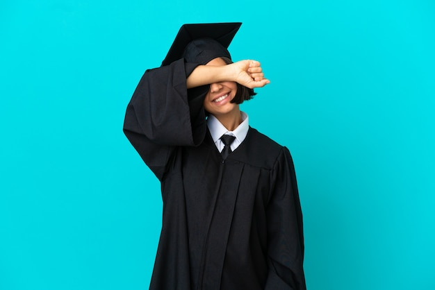 Young university graduate girl over isolated blue background covering eyes by hands