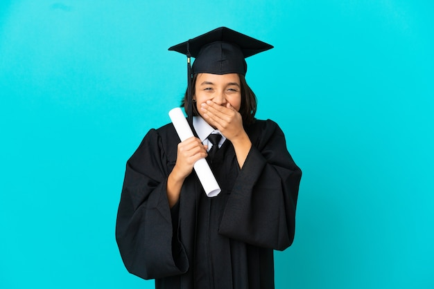 Young university graduate girl over isolated blue background happy and smiling covering mouth with hands