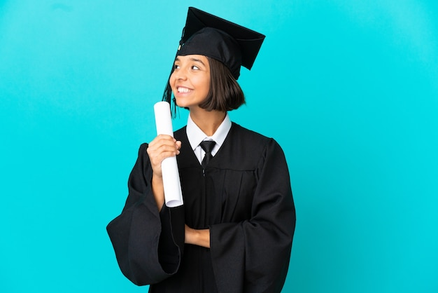 Young university graduate girl over isolated blue background happy and smiling