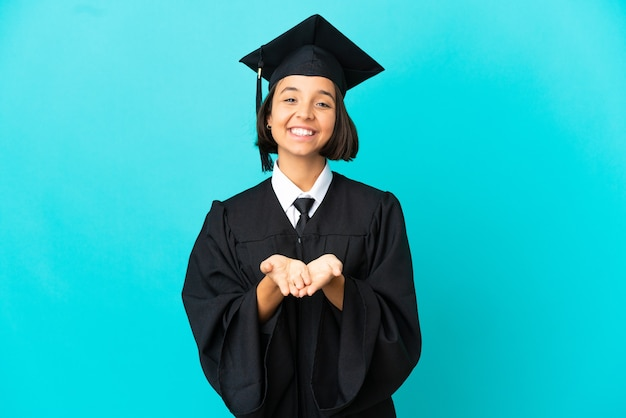 Young university graduate girl over isolated blue background holding copyspace imaginary on the palm to insert an ad
