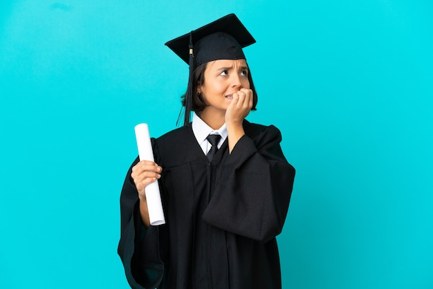Young university graduate girl over isolated blue background is a little bit nervous