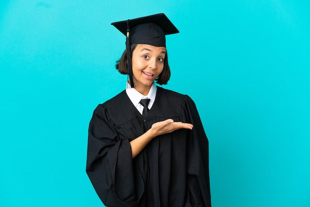 Young university graduate girl over isolated blue background presenting an idea while looking smiling towards